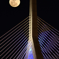 Boston landmark photography of the rising full moon over the historic Boston Zakim Bridge in Charlestown Massachusetts. <br />