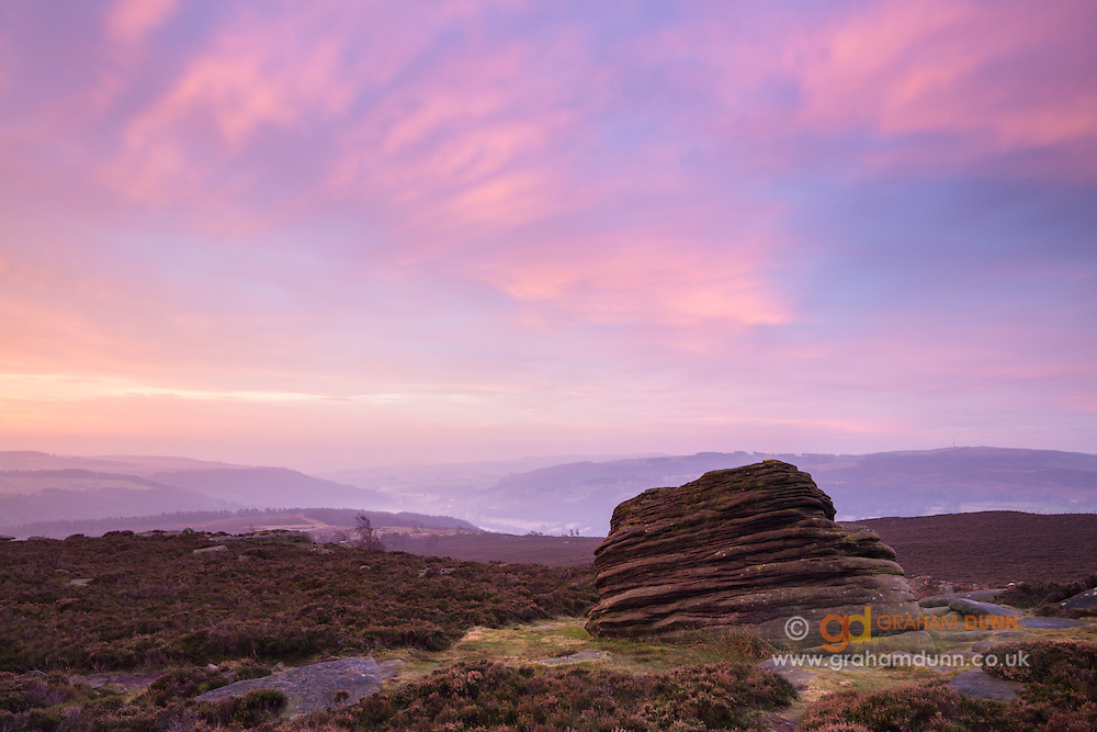 Colourful dawn skies hang over a striped rock formation at Over Owler Tor on Hathersage Moor. Overlooking the Derwent Valley. Autumn sunrise, December. Peak District National Park, Derbyshire, England, UK.