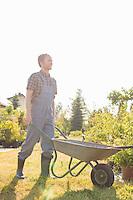Full-length of man pushing wheelbarrow at garden