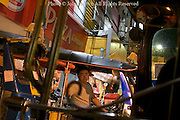 A male tuk tuk driver is waiting for customers at night on a city street in Chiang Rai, Thailand.