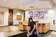 Monica Nezzer spreads cream-cheese on her bagel, a quick breakfast before starting work on Thursday June 2, 2016. Monica Nezzer and Patrick Arite are both students at the University of New Mexico and are working 15-30 hours per week giving campus tours in order to help put themselves through college. (Steven St. John for NPR)