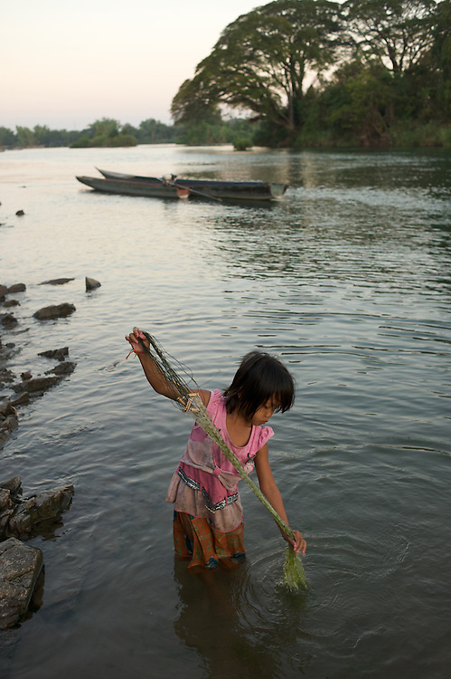 A young girl spends some time in the morning checking for fish caught overnight and then cleaning her net.  She had procured a few small fish the night before.