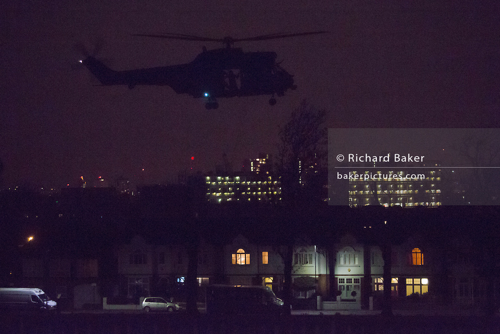 A Puma helicopter (one of a pair) takes-off from Ruskin Park at 10.50pm, on 6th March 2017, in the London borough of Lambeth, England. Pumas in ones or twos occasionally land for a few minutes with engines running before departing again for other destinations. It's believed these landings help train flight crews for future evacuation of VIPs in times of emergency using open space locations like public parks. On this occasion, the two aircraft landed with lights off (so perhaps using night-vision) in the darkness.
