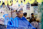 A male barber is cutting a boys's black hair in a barbershop in Chiang Rai, Thailand.