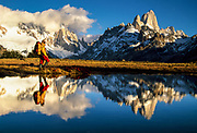 Trekker reflected in pond under Cerro Torre (left) & FitzRoy, Los Glaciares National Park, Patagonia, Argentina
