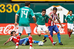 March 26, 2011; Oakland, CA, USA;  Mexico forward Pablo Barrera (7) dribbles past Paraguay forward Edgar Benitez (10) during the first half at Oakland-Alameda County Coliseum. Mexico defeated Paraguay 3-1.