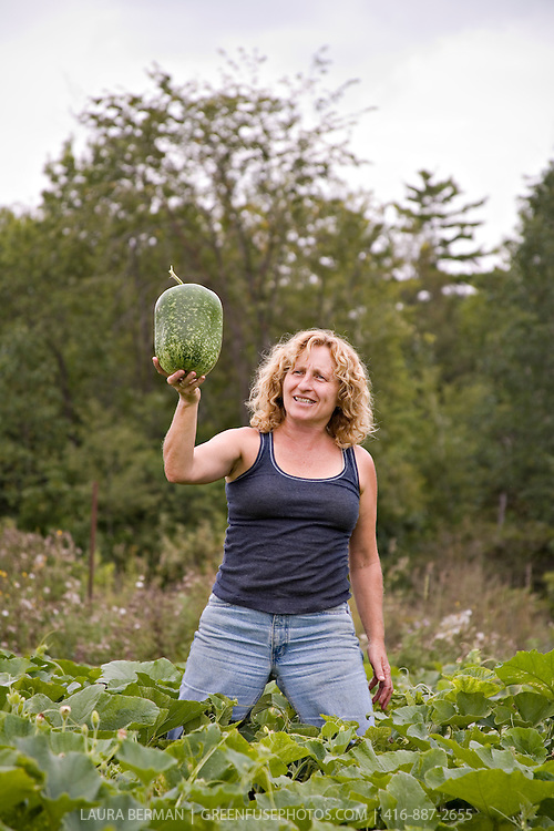 Farmer Kim Delaney proudly shows off an example of her squash harvest.