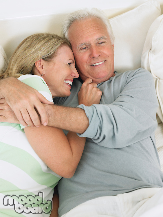 Couple embracing lying on bed elevated view