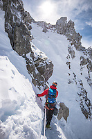 A back-view on a male mountaineer traversing a snow field on the slope of Aiguille Marbrees.