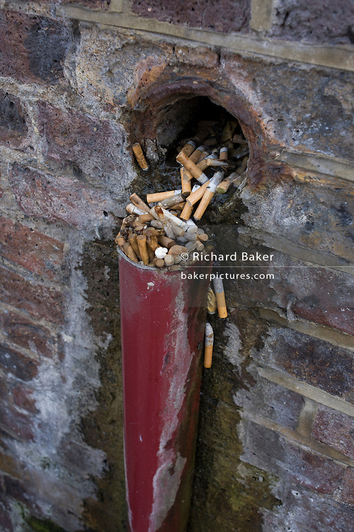 Discarded cigarettes spill from a hole in a brick wall in Waterloo, south London.