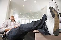 Casually dressed Businessman reclining with feet on desk  Listening to Music With Headphones