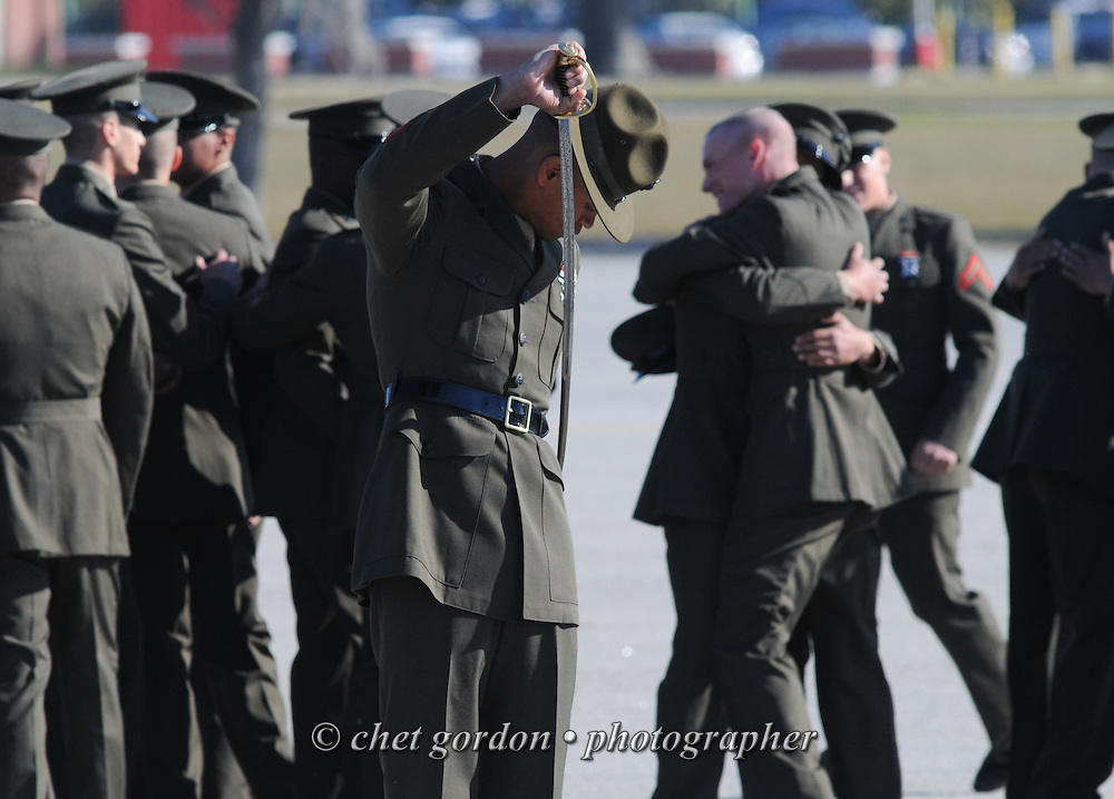A Marine Corps Drill Instructor (center) secures his sword as his platoon of new Marines celebrate after being dismissed during graduation at the Marine Corps Recruit Depot (MCRD) in Parris Island, SC  on Friday morning, March 15, 2013.