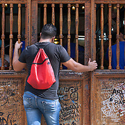 Taking a look at the action from the outside at the famous bar La Bodeguita del Medio in La Habana Vieja. . Cubans manage their daily life waiting for overcrowded busses or doubling up on old classic cars and motorcycles or walking everywhere.  <br />