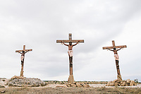 """MATERA, ITALY -6 OCTOBER 2019: The scene of the crucifixion of Jesus Christ, performed by  Yvan Sagnet (34, center, a political activist and former exploited tomato farmer) and the two thieves is filmed during the production of """"The New Gospel"""", a film by Swiss theatre director Milo Rau, in Matera, Italy, on October 6th 2019.<br /> <br /> Theatre Director Milo Rau filmed the Passion of the Christ  under the title """"The New Gospel"""" with a cast of refugees, activists and former actors from Pasolini and Mel Gibson's films.<br /> <br /> The role of Jesus is performed by Yvan Sagnet, a Political activist born in Cameroon and who worked on a tomato farm when in 2011 he revolted against the system of exploitation and led the first farm workers' strike in southern Italy. In a series of public shoots in the European Capital of Culture Matera, Jesus will proclaimed the Word of God, was crucified (October 6th 2019) and finally rose from the dead in Rome, the capital of Catholic Christianity and seat of one of the most xenophobic governments in Europe (October 10th 2019).<br />  <br /> Parallel to the film, the humanistic message of the New Testament was transformed into the present: at the beginning of September, the campaign """"Rivolta della Dignità"""" (Revolt of Dignity), which demanded fair working and living conditions     for refugees, global freedom of travel and civil rights for all, started with a march from the southern Italian refugee camps. """"It's about putting Jesus on his feet,"""" director Milo Rau said. Led by Jesus actor Yvan Sagnet, the campaign fights for the rights of migrants who came to Europe via the Mediterranean to be enslaved by the Mafia in the tomato fields of southern Italy and to live in ghettos under inhumane conditions. The campaign and the film thus create a """"New Gospel"""" for the 21st century, a manifesto of solidarity with the poorest, a revolt for a more just and humane world."""