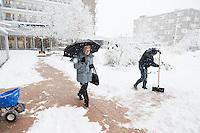 Nederland, Rotterdam, 17 december 2010. Weeralarm, zware sneeuwval in de Randstad. Medewerkers van bejaardentehuis Humanitas, gekleed in dikke winterkleding en mutsen, maken het trottoir naar de ingang van het ouderenhuis vrij van sneeuw. Bejaarde dame maakt dankbaar gebruik van het schoongemaakte deel op de stoep. Wegscheppen van sneeuw, pad maken in de sneeuw. Foto: David Rozing