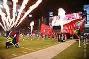 Fire  frames the player tunnel as cheerleaders line up and a team flag bearer runs onto the field leading the players onto the field before the Arizona Cardinals 2016 NFL preseason football game against the Oakland Raiders on Friday, Aug. 12, 2016 in Glendale, Ariz. The Raiders won the game 31-10. (©Paul Anthony Spinelli)