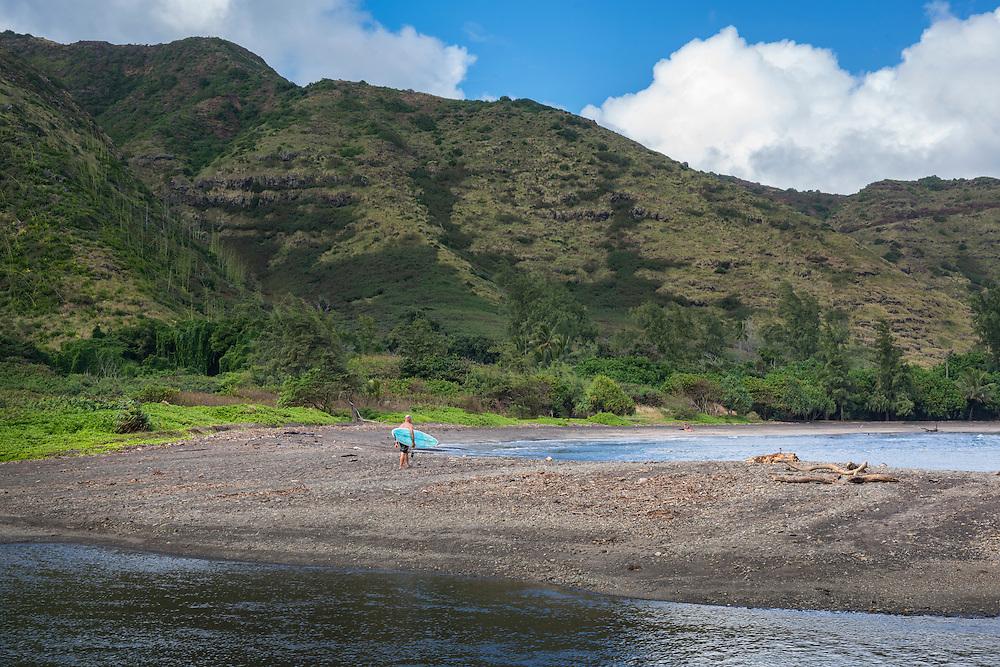 USA, Hawaii, Molokai, tropical,Halawa valley, man with surf board walking across stream