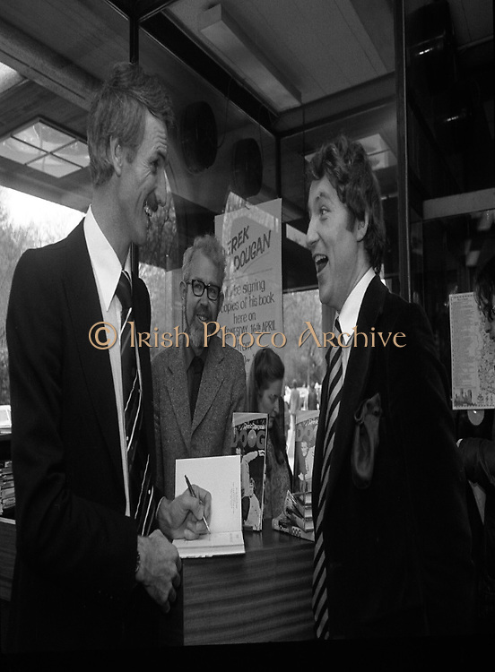 Derek Dougan's name goes in the book...1980-04-16.16th April 1980.16-04-1980.04-16-80..Photographed at Hodges Figgis, Stephen's Court, St Stephen's Green, Dublin:..Fromer Northern Irish soccer international and English League player Derek Dougan signing a copy of his book 'Doog' for customer Peter Jones, Adelaide Road, Dublin...Also in picture..Robert Twigg, manager of Hodges Figgis .