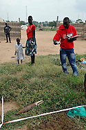 A MAG community liaison team mark a rocket as local residents look on in an area where a huge number of unexploded ordinance were found just opposite John Garang's tomb in Juba as the area was being prepared for South Sudan independence ceremonies. The Government of South Sudan called on Mines Advisory Group (MAG) to assist SPLA deminers in an attempt to clear the area and make it safe for the thousands of people and dignitaries who will be attending the declaration of independence on July 9th..Juba, South Sudan. 04/07/2011..Photo © J.B. Russell