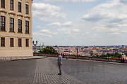 "A man standing at empty ""Hradcany Square"" (Hradcanske Namesti) towards the panoramic view at the Prague cityscape. On the left Prague Castle. The Czech government lowered the security measures and as of Monday 25 May 2020, wearing of protective masks will be mandatory only in the interiors of buildings other than the place of residence and in public transport."