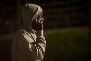 An African migrant speaks on the phone before heading to France crossing the Spanish-French border walking along Santiago bridge. Irun (Basque Country). August 22, 2018. As the number of migrants arriving on the coasts of southern Spain incresead, more and more migrants are heading north to the border city of Irun. (Gari Garaialde / Bostok Photo)