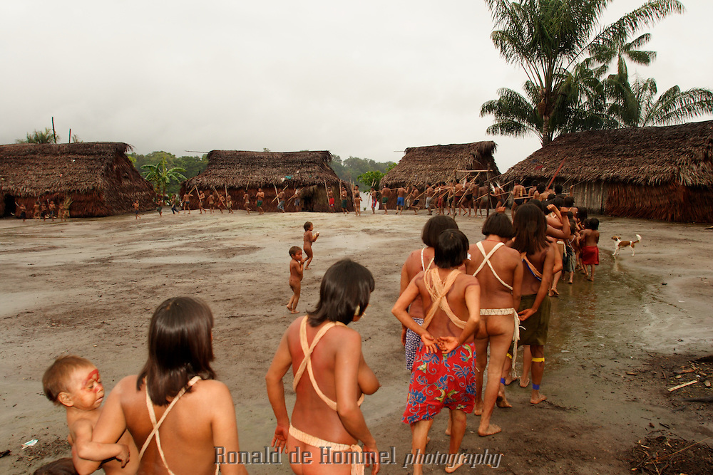 Viriunaveteri, Venezuela. Yanomami women dancing a tribal dance. The village of Viriunaveteri consists of 15 huts around a muddy square. It's situated in the Venezuelan Amazone several days by boat from the nearest town. This community on the banks of the Casiquiare is one of the few Yanomami villages that actually has some contact with the outside world. Most other tribes live deeper in the jungle.