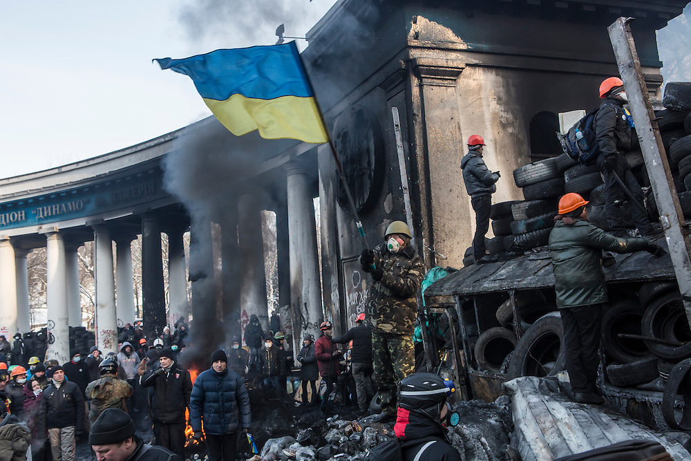 KIEV, UKRAINE - JANUARY 25: An anti-government protester waves a Ukrainian flag during clashes with police on Hrushevskoho Street near Dynamo stadium on January 25, 2014 in Kiev, Ukraine. After two months of primarily peaceful anti-government protests in the city center, new laws meant to end the protest movement have sparked violent clashes in recent days. (Photo by Brendan Hoffman/Getty Images) *** Local Caption ***