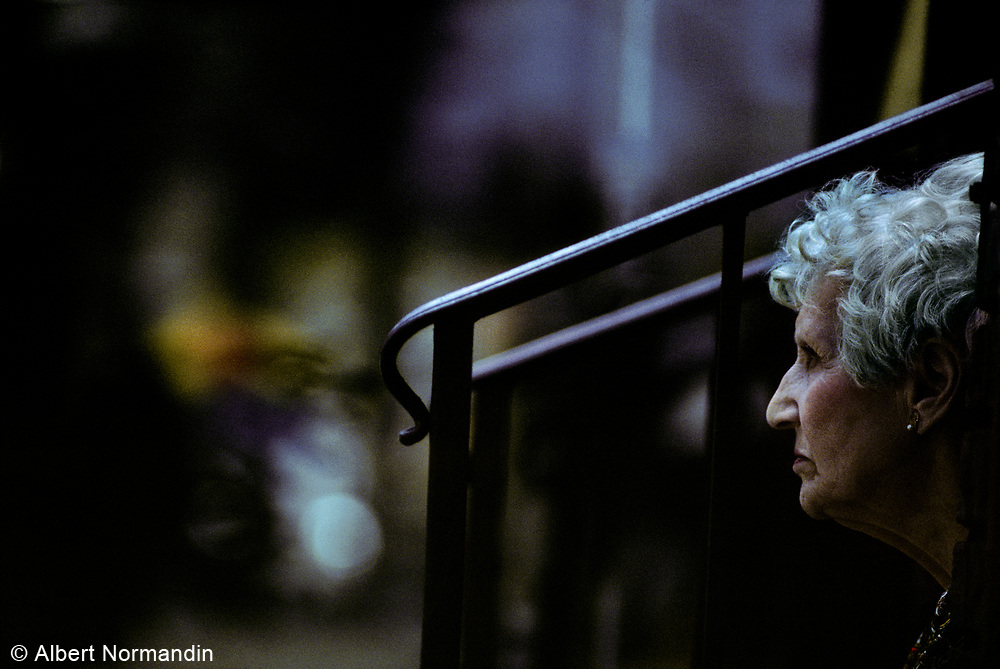 Old grey haired woman sitting on steps on The Bowery