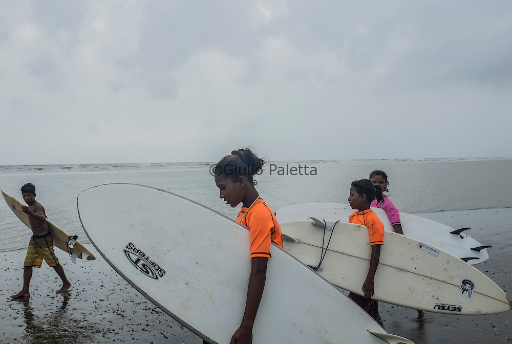 Getting ready for surfing on Cox's Bazar's beach. Checking the waves