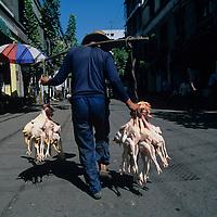 China, Fengjie, Man carries dead ducks through street market in Yangzi River city of Fengjie