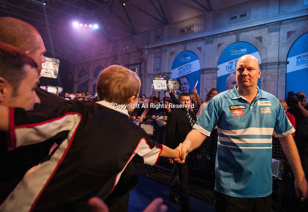 02.01.2014.  London, England.  William Hill PDC World Darts Championship.  Quarter Final Round.  Vincent van der Voort (23) [NED] shakes hands with a fan as he makes his way to the stage before his match with Phil Taylor (2) [ENG]