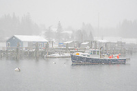 A lobster boat sits on its mooring in the snow in Owls Head Harbor.