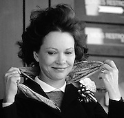 First Lady of the United states, Rosalynn Carter, deals with a flyaway scarf at an outdoor state event.