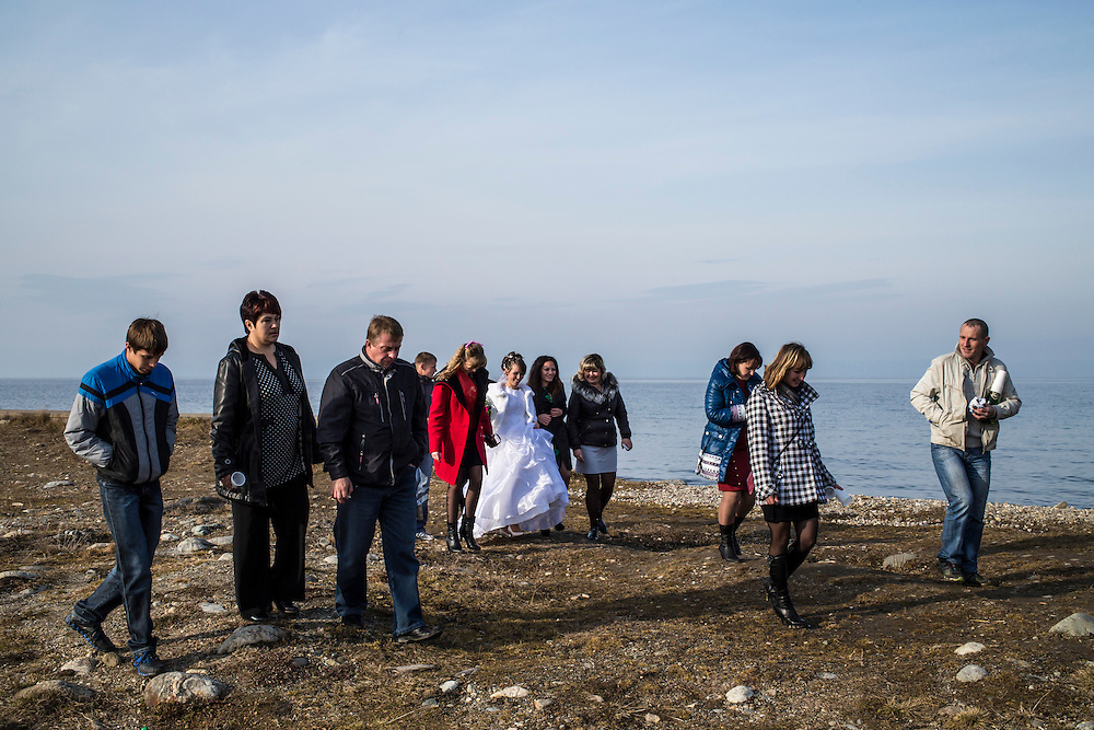 Tatiyana and Nikolai walk with friends and family on the shore of Lake Baikal on their wedding day on Friday, October 25, 2013 in Baikalsk, Russia.