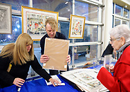 Garden City, New York, USA. March 9, 2019.  Artist Michael White (standing) helps as woman at right purchases one of his carousel watercolor prints during Unveiling Ceremony of his mural of Nunley's Carousel horse closeup. Event was held at historic Nunley's Carousel in its Pavilion on Museum Row on Long Island.