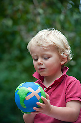 young boy holding a model of a sick planet Earth with a band-aid stuck on it