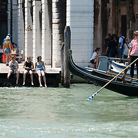 A gondolier look at a group of teenager resting with their feet in the Grand Canal on the day the Italian Government and Heath Ministry has issued several warning for the current heath wave