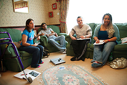Group of students, including one with Cerebral Palsy (CP), who uses walking frame, studying at home watching an educational DVD