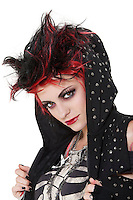 Close-up portrait of young punk woman wearing hood over white background