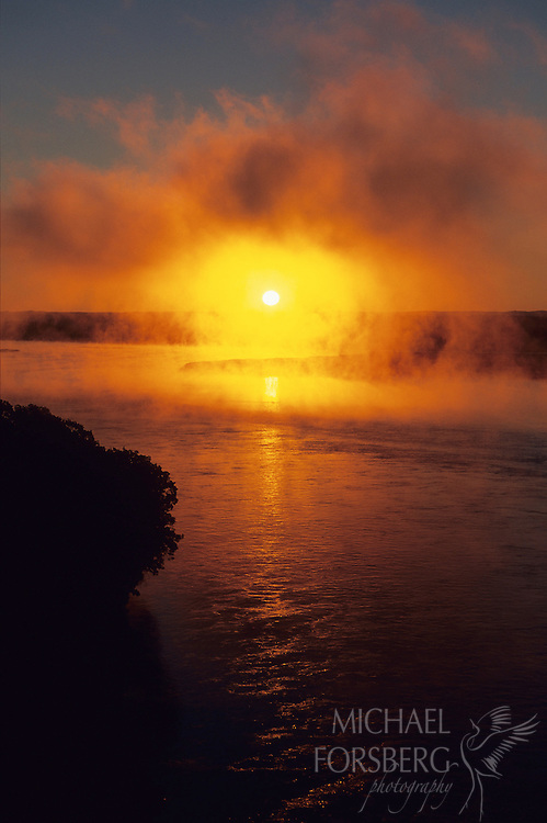 The morning sun cuts through heavy fog floating above the Missouri River on the Nebraska-South Dakota border.
