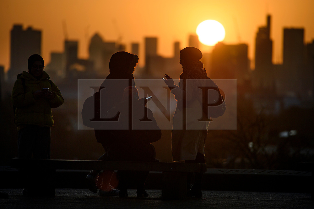 © Licensed to London News Pictures. 11/02/2020. London, UK. People watch the sun rises from behind the City of London, seen from Primrose hill in North London. Large parts of the UK are recovering from the affects of storm Ciara which caused heavy flooding and damage from high winds. Photo credit: Ben Cawthra/LNP