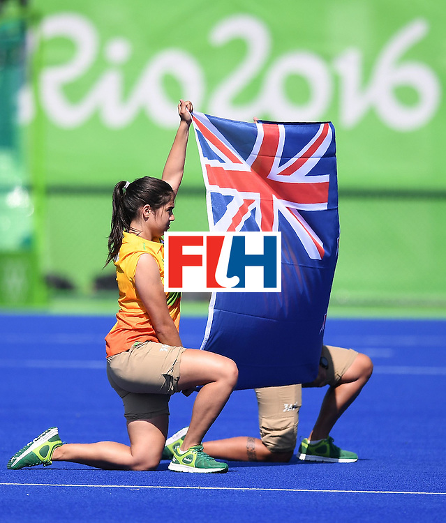 A volunteer holds up a New Zealand flag during the men's field hockey Australia vs New Zealand match of the Rio 2016 Olympics Games at the Olympic Hockey Centre in Rio de Janeiro on August, 6 2016. / AFP / MANAN VATSYAYANA        (Photo credit should read MANAN VATSYAYANA/AFP/Getty Images)