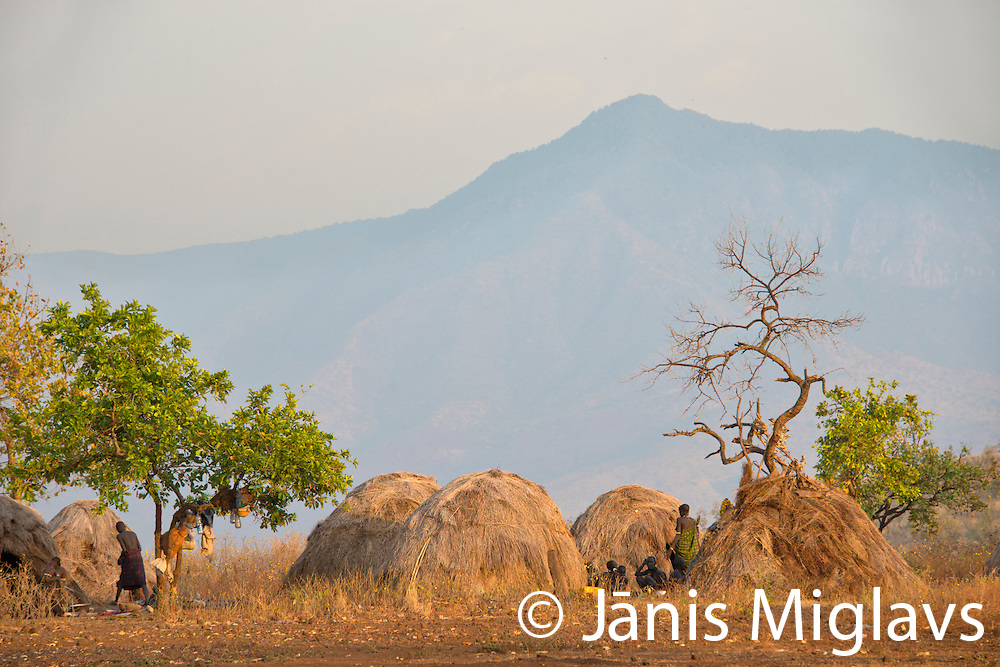 Grass huts of Belle, a Mursi tribe village in front of mountain in Mago National Park, Omo Valley, Ethiopia, Africa.