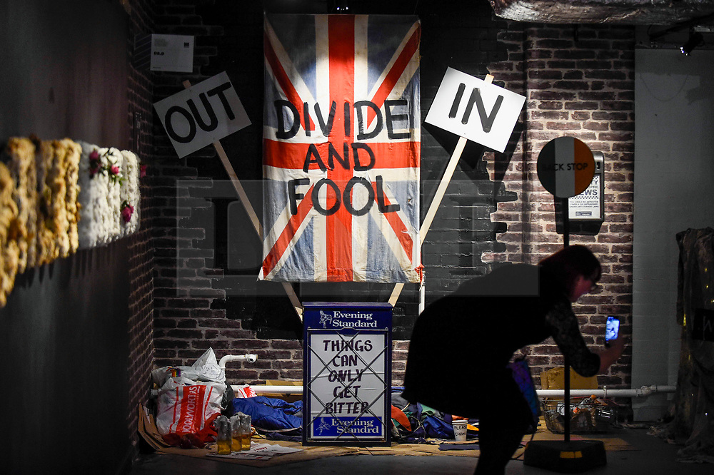 © Licensed to London News Pictures. 04/10/2019. LONDON, UK. A visitor views a Brexit related installation by Dr. D at the George The Union Is Cross stand at the Moniker International Art Fair, an urban contemporary art fair taking celebrating its 10 year anniversary in the UK.  The fair is  place at Chelsea's Sorting Office air until 6 October 2019.  Photo credit: Stephen Chung/LNP