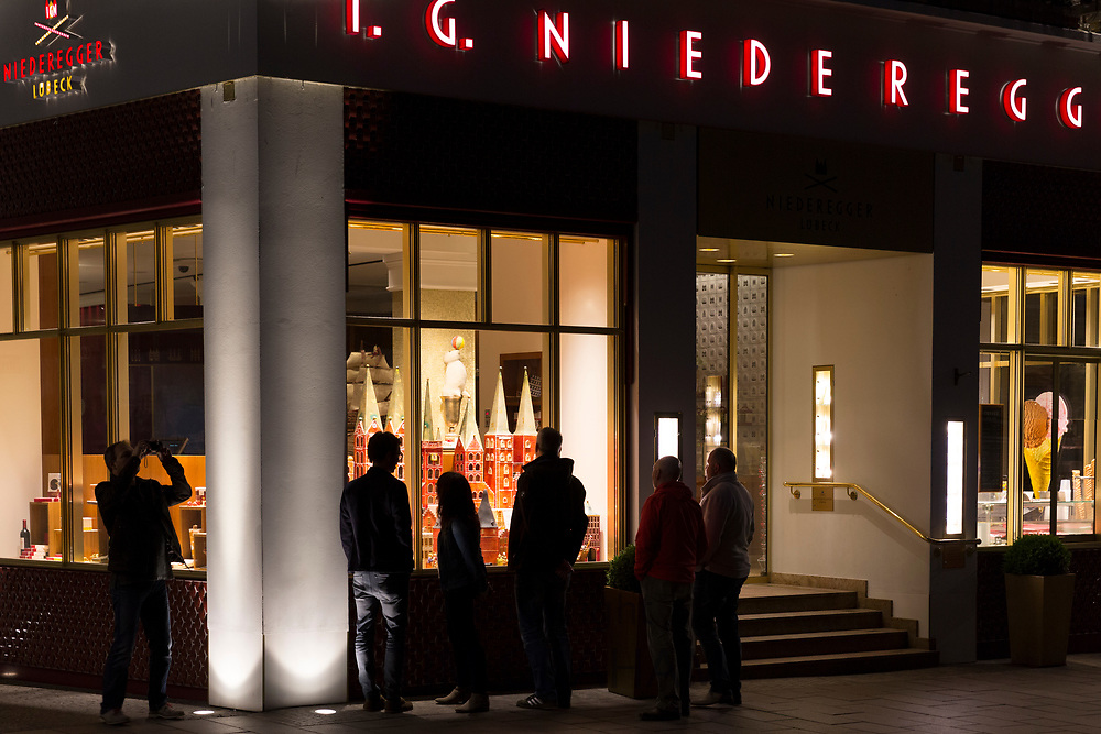 Tourists looking at shop window display at J.G. Niederegger famous marzipan candy shop in Lubeck, Germany