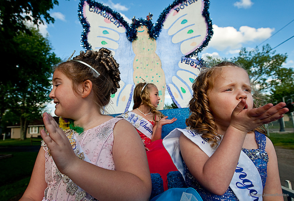 Atop their float and in the final leg of the parade route during McArthur's Turkey Festival, from left, Hannah Lanning, 8, Heidi Jo McGrady, 6, and Tomi Sue Shweikert, 5, wave and smile to empty streets on the way home, on Saturday morning, May 9, 2009, in Ohio.
