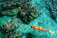 Aerial view of female snorkeler wearing a yellow one piece swimsuit.