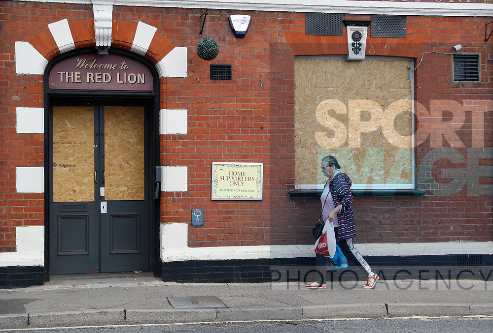 A woman walks past a boarded up pub which used to open for the home fans before the Premier League match at Vicarage Road, Watford. Picture date: 20th June 2020. Picture credit should read: Darren Staples/Sportimage