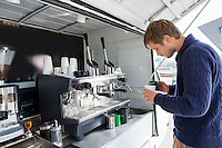 Profile shot of man pouring milk in cup at mobile coffee shop