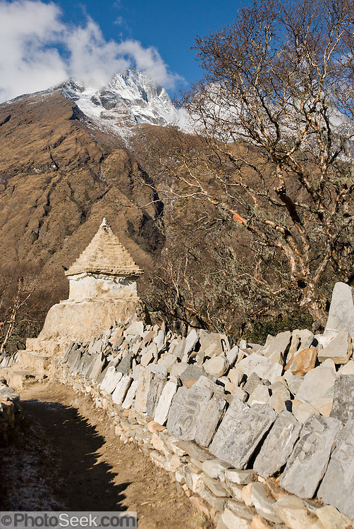 A mani stone wall, Phortse village, and the peak of Khumbila (18,900 feet / 5761 meters; or Khumbi Yul Lha), in the Himalaya of eastern Nepal. Because local Sherpa people traditionally consider Khumbila to be a sacred warrior spirit and guardian of the Khumbu District, Nepal has declared this mountain illegal to climb. Sagarmatha National Park was created in 1976 and honored as a UNESCO World Heritage Site in 1979.